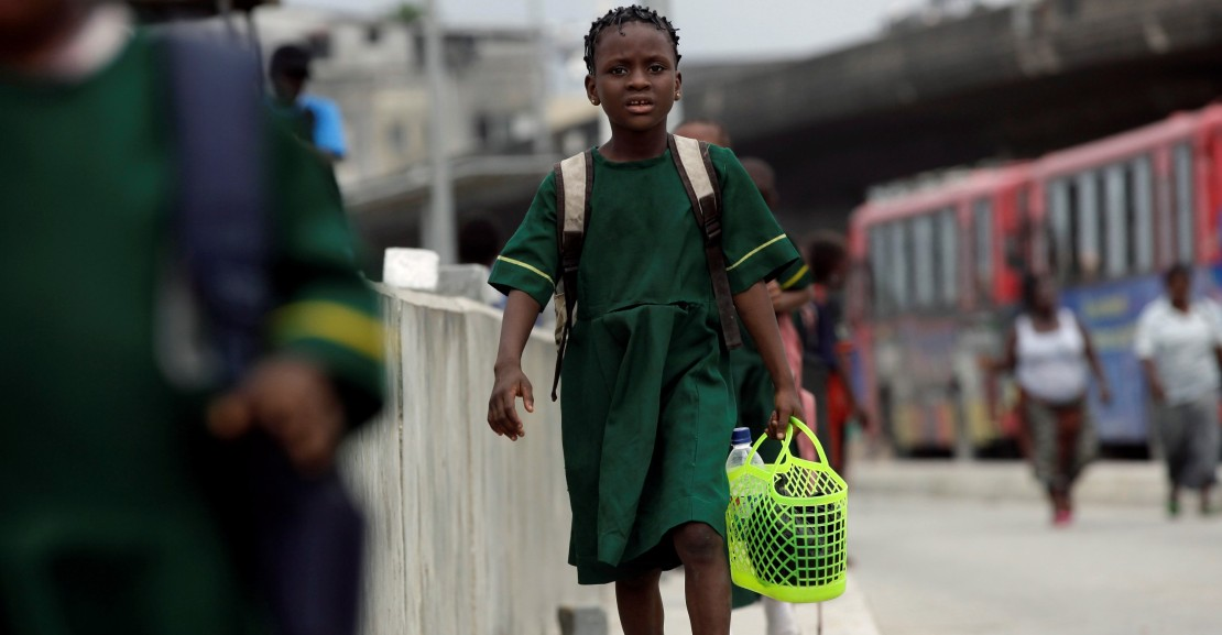 An unidentified school girl walk past a bus park, on the first International Day of the Girl Child, in Lagos, Nigeria, Thursday, Oct. 11, 2012. The UN has declared October 11th as the International Day of the Girl Child. Girls face double discrimination due to their gender and age, and are the most marginalized and discriminated group across the globe.(AP Photo/Sunday Alamba)